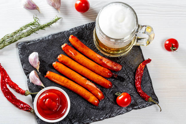 Top view of a light beer with spices and grilled sausages