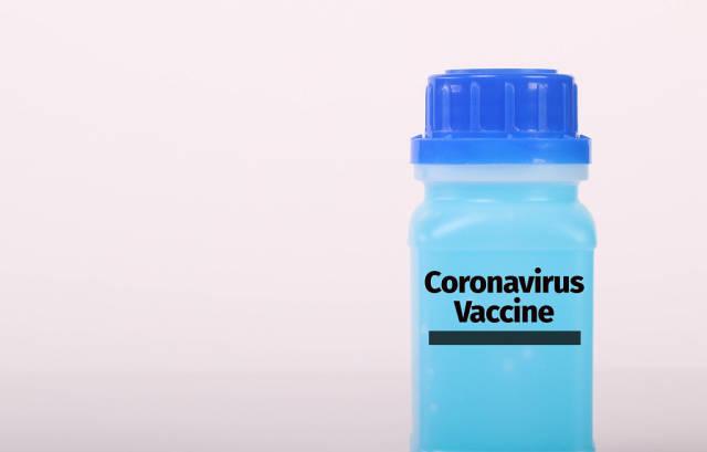 Bottle with blue fluid and Coronavirus Vaccine text