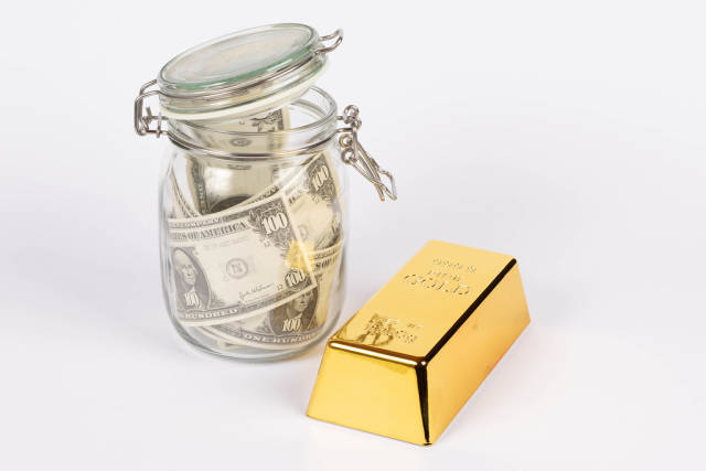 Dollar bills in glass jar with gold bar on white background