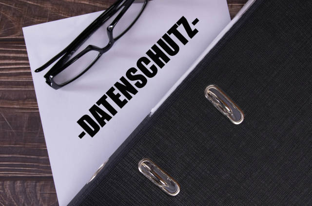 Office folder with glasses and Datenschutz text on wooden table