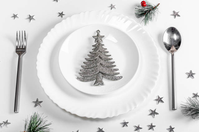 Plates with spoon and fork on a white table with Christmas silvery decor