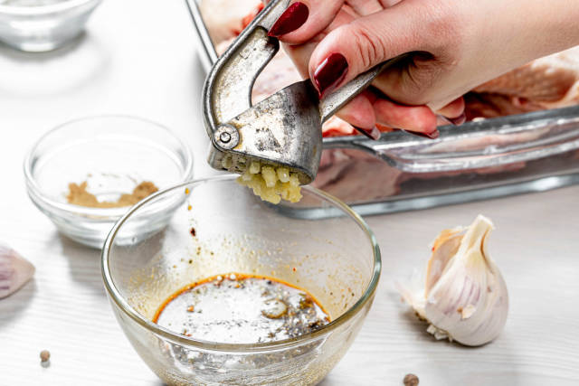 The cook squeezes the garlic with a garlic grinder into the marinade sauce