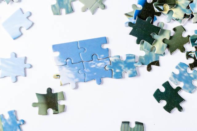 Puzzleteile und erste verteilt um begonnenes Puzzle vor weißem Hintergrund