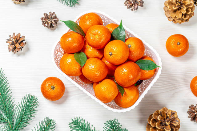 Top view of Christmas background with tangerines, pine cones and branches Christmas tree
