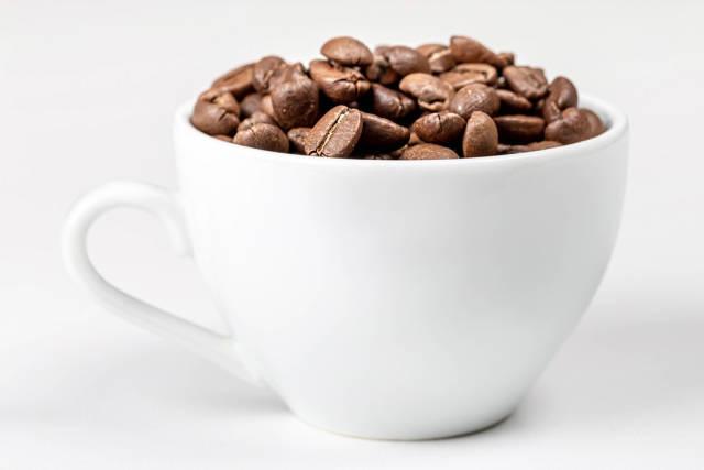 Eine weiße Tasse voll mit gerösteten Kaffeebohnen