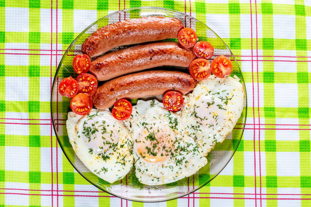 Scrambled egg with sausages and cherry tomatoes