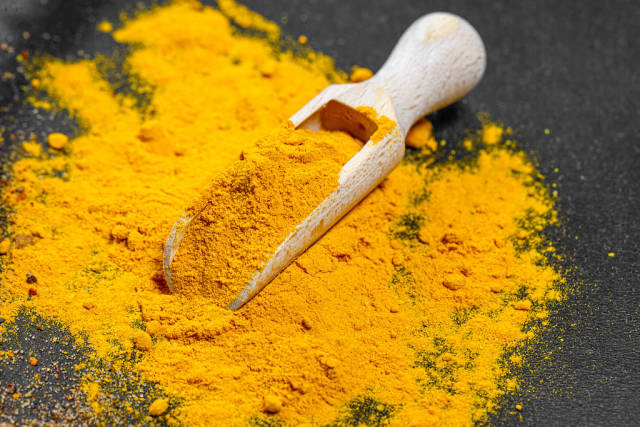Ground turmeric in wooden scoop on black background
