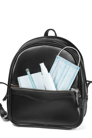 Back to school after quarantine concept. Backpack with school supplies and sanitizer and medical protective mask