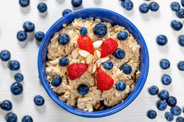 Top view oatmeal porridge with blueberries, almonds and strawberries on a white wooden background