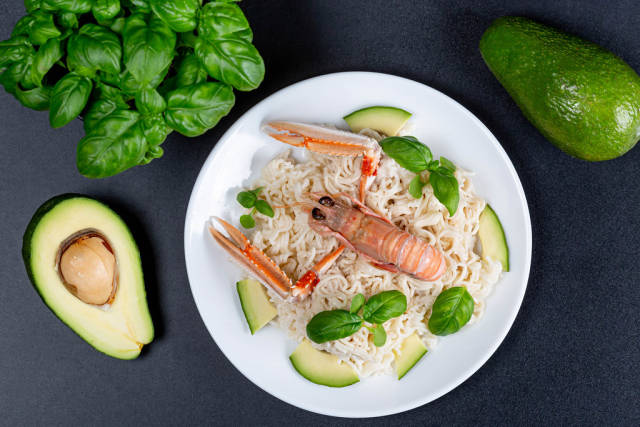 Top view, noodles with lobster, avocado and basil on a black background