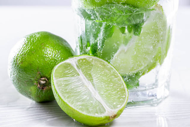 Close-up of half and a whole a lime and a glass of Mojito behind