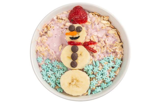 Top view, oatmeal with strawberry yogurt and banana snowman