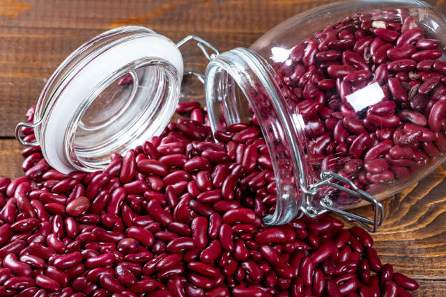 A jar of red beans on a wooden table