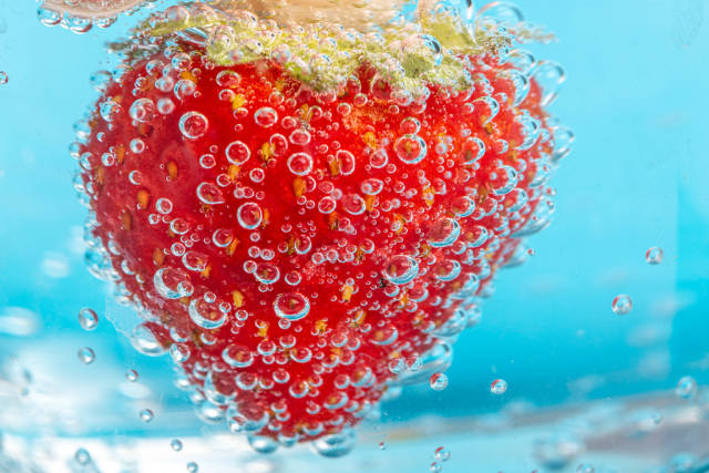 Strawberries on blue background with bubbles