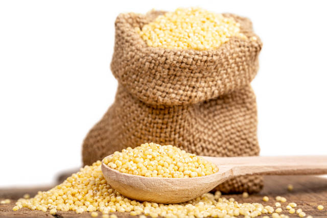 Millet in a wooden spoon with a bag behind