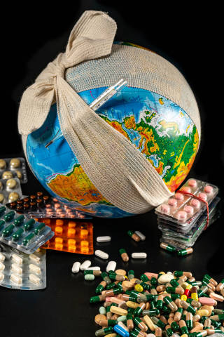 Lots of medical drugs pills and capsules on a dark background with a globe in an elastic bandage