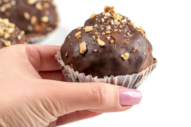 Female hand with chocolate cake, close -up