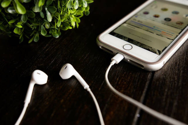 Iphone and earphones on a wooden table