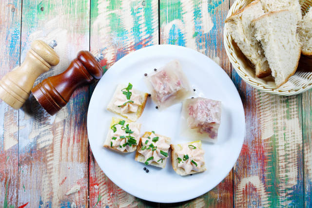 Pork jelly served with homemade bread, salt and pepper. Wooden vintage background