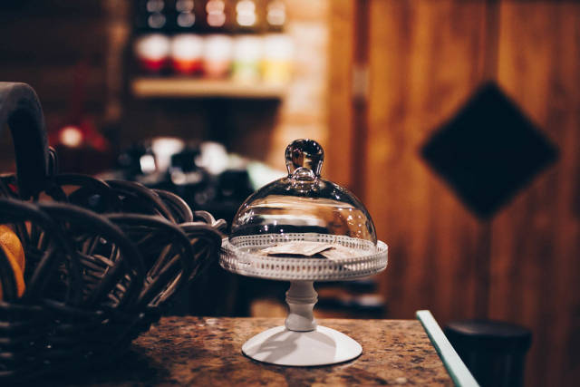 Small glass tray with lid on blurry background. Cafe interior