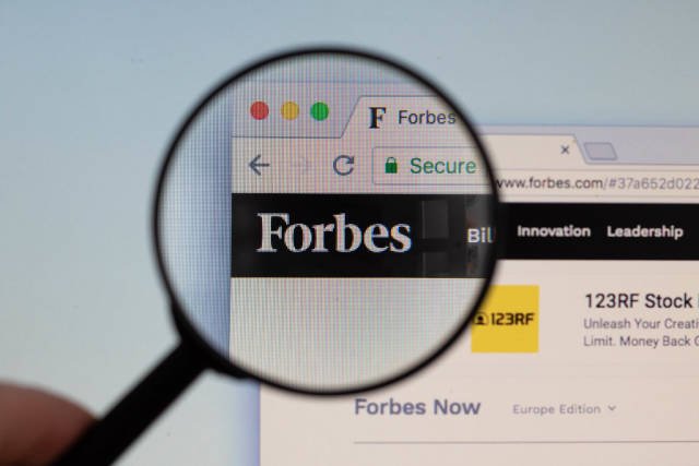 Forbes logo on a computer screen with a magnifying glass