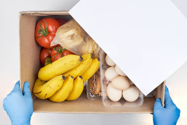 A person in protective medical gloves holds a donation box with food items for a food pantry delivery