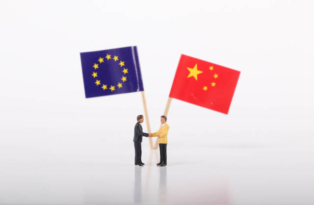 Two businessman shaking hands in front of flags of European Union and China