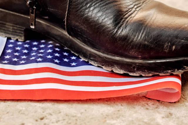 Fuß in einem schwarzen, dick besohlten Stiefel tritt mit Verachtung auf eine amerikanische Flagge