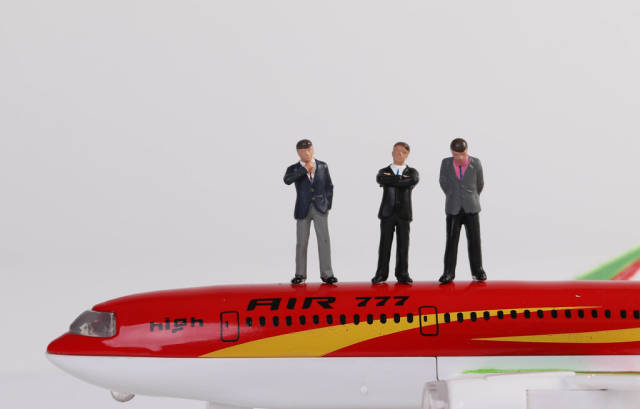 Miniature people businessman in suit and tie standing on toy airplane