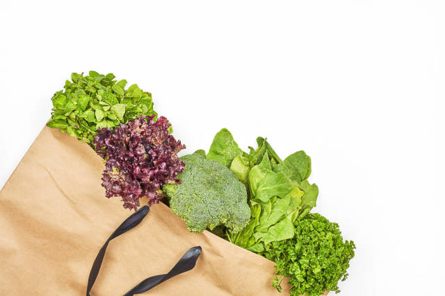 Paper bag with green leafy vegetables salad on white background