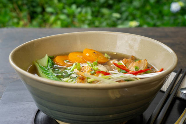 Close Up Food Photo of Japanese Ramen Noodle Soup with Pork, Spring Onions, Bok Choy and Sliced Carrots in a Ceramic Bowl on a Wooden Table with Chopsticks