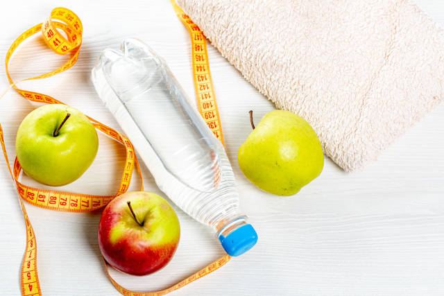 Water bottle, apples, measuring tape and towel on white wooden background. Top view