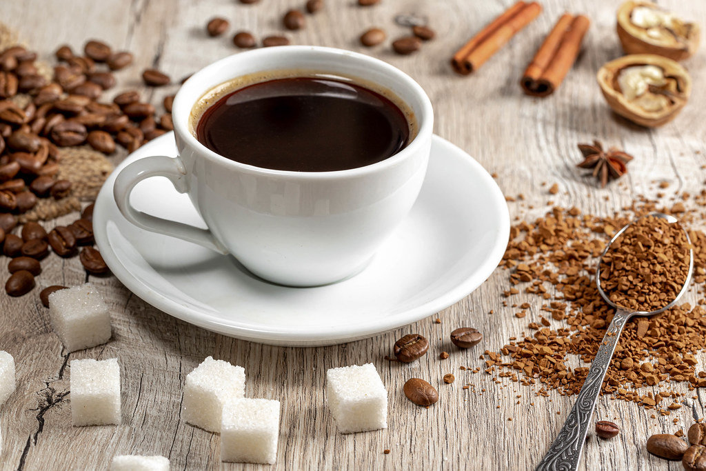 Coffee cup and beans on wooden table with spices, ground coffee and sugar cubes