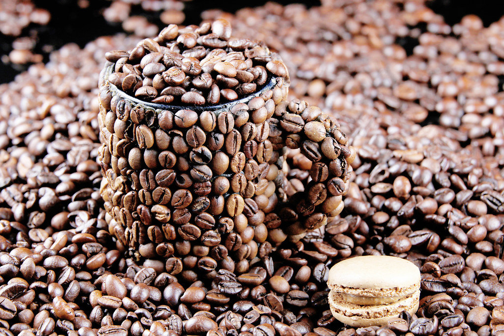 Cup of coffee beans and a macaron cake