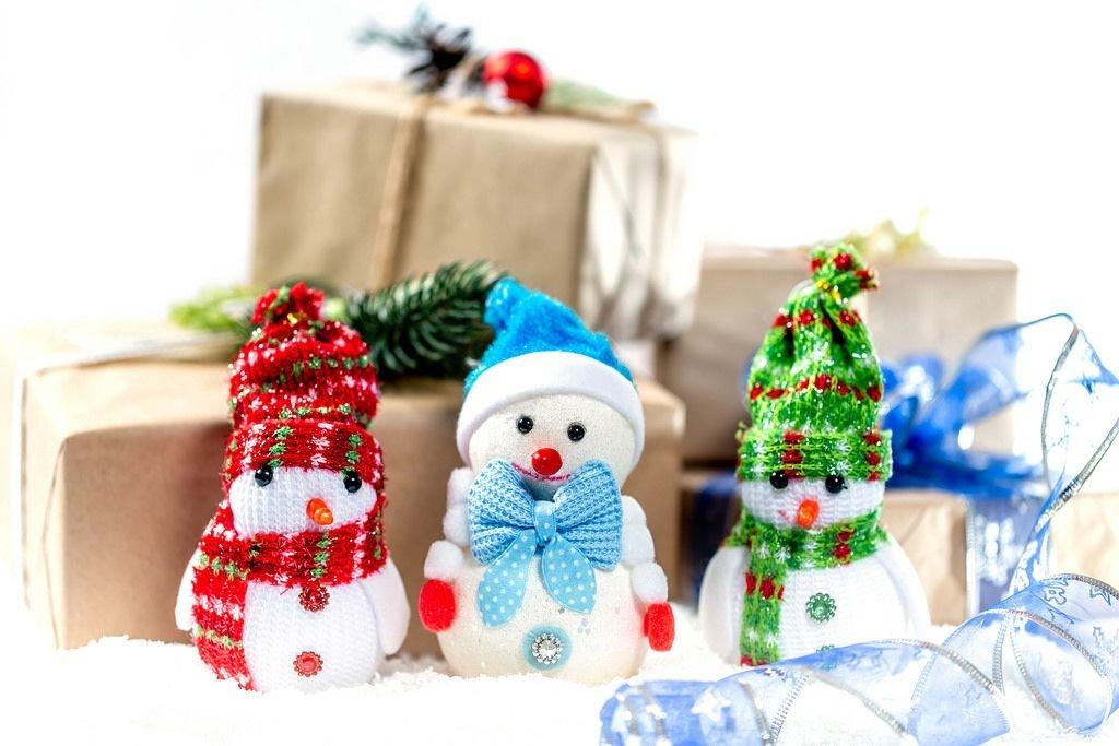 Drei kleine Schneemänner mit Mütze und Schal vor Weihnachtsgeschenken im Schnee