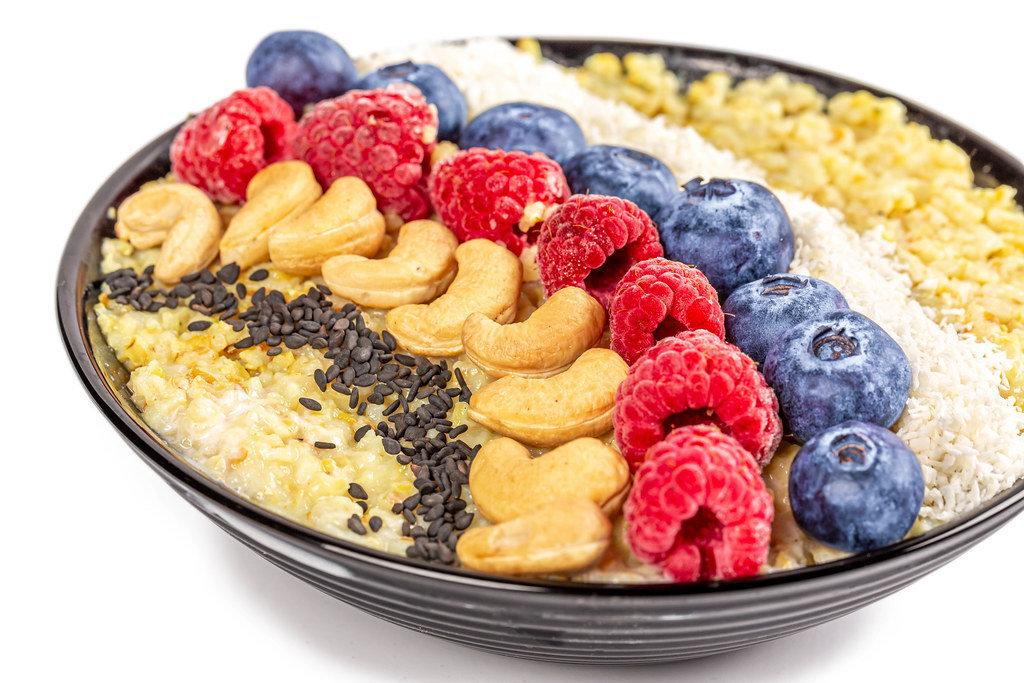 Close-up, porridge with black sesame seeds, cashews, raspberries, blueberries and coconut flakes