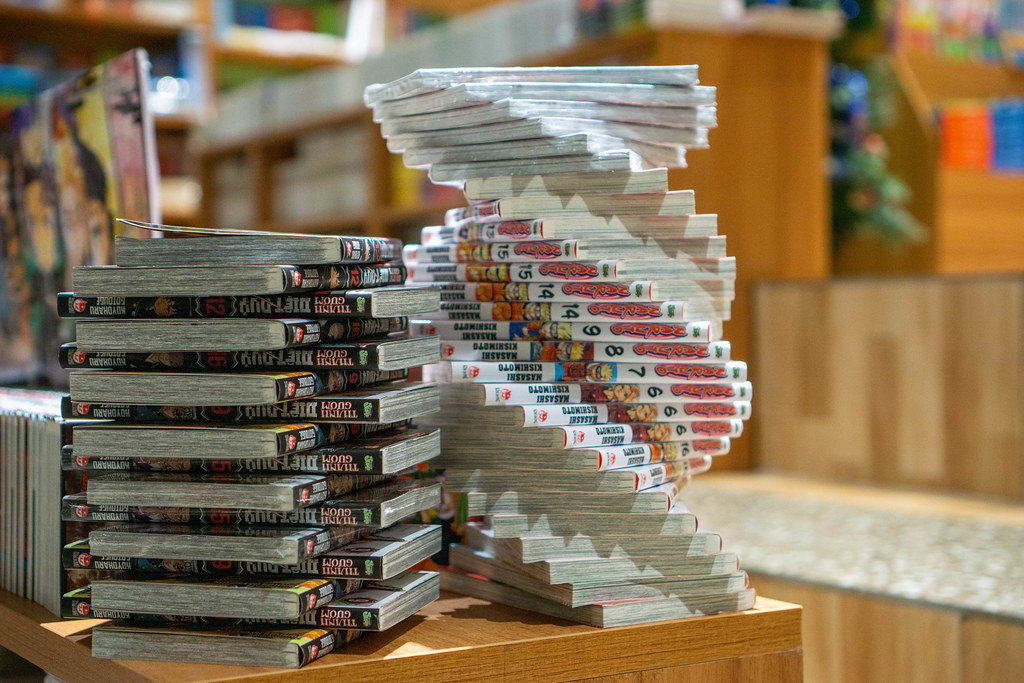 Bokeh Photo of Spiral of Manga Books of the Series Naruto next to a Stack of Comic Books in a Bookstore