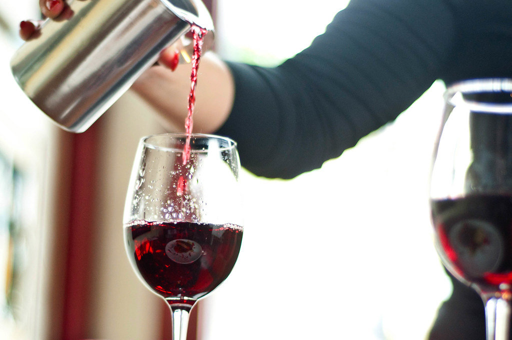 Closeup photograph of red wine poured in wineglass at a fancy restaurant