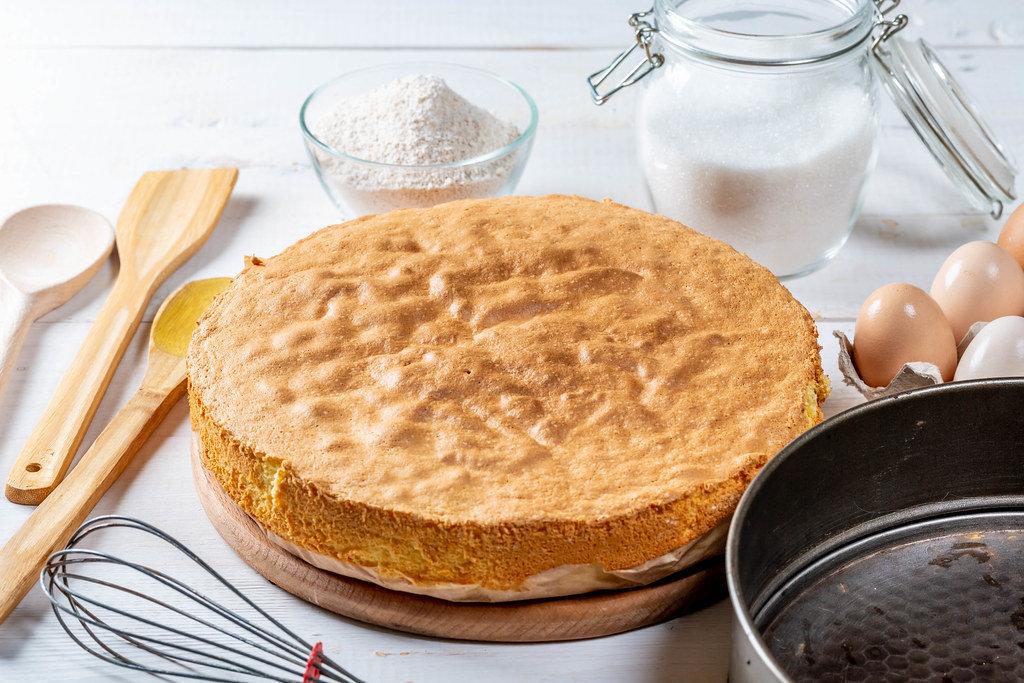 Biscuit, eggs, sugar, flour with baking dish and wooden kitchen utensils