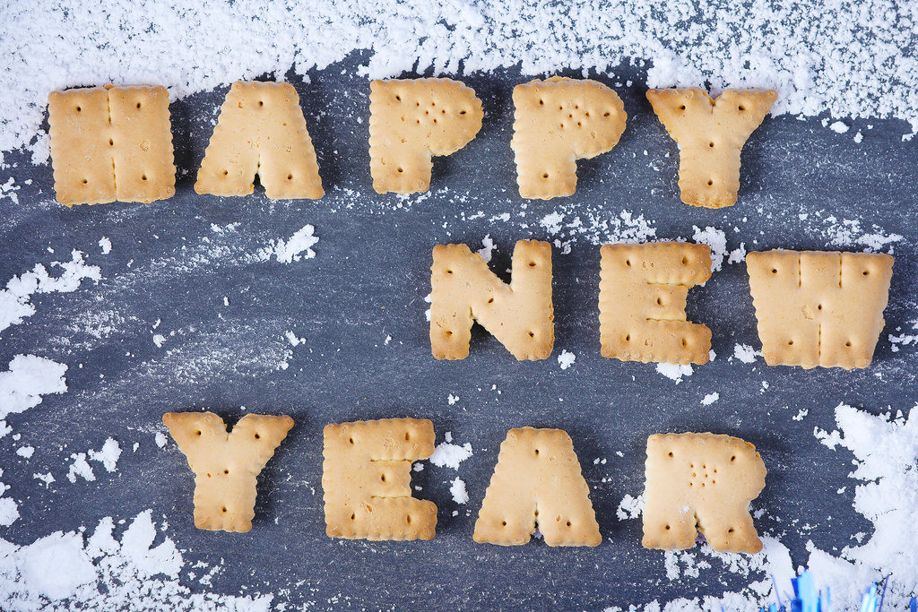 Happy New Year message, written with biscuit letters, snow