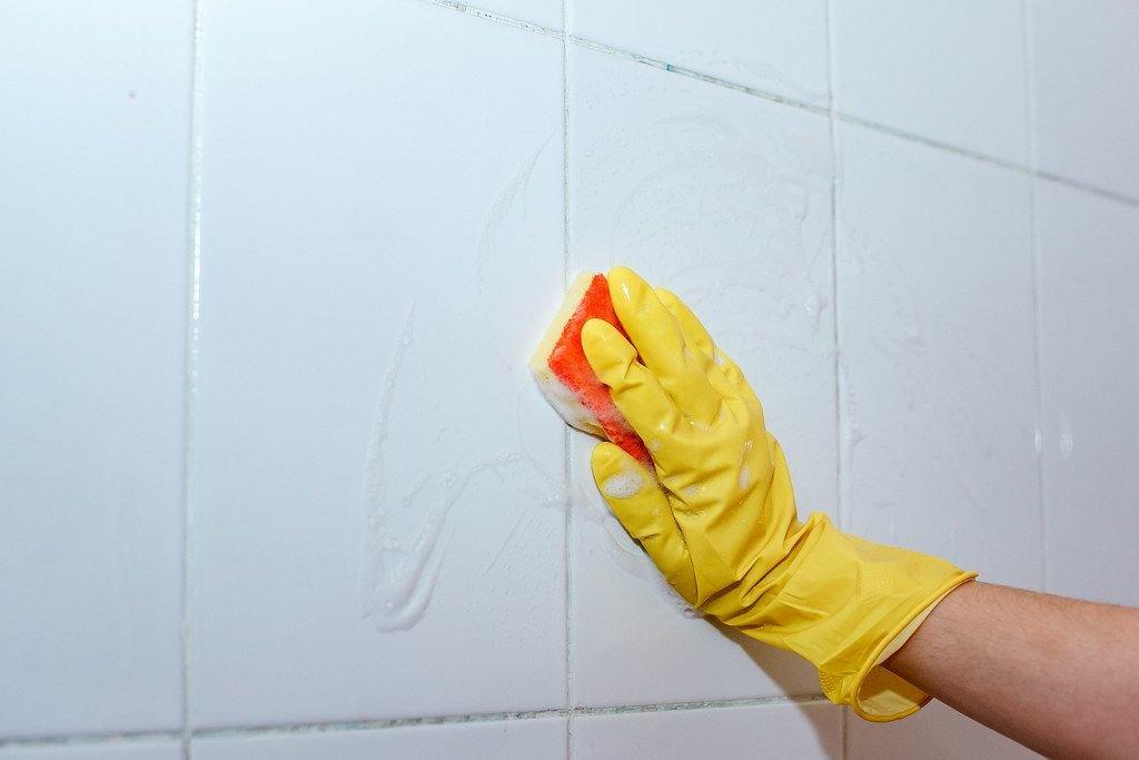 Hausmädchen reinigt die Badezimmer-Fliesen mit einem Schwamm und Latexhandschuhen