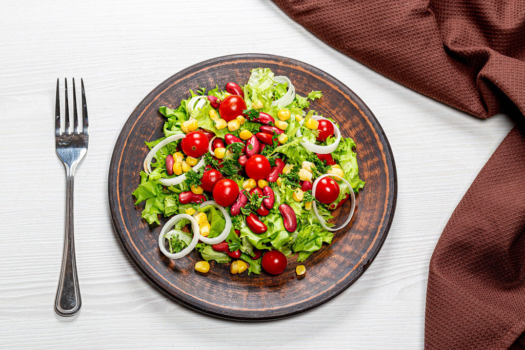 Diet salad with vegetables and red beans in a brown plate with a fork and a kitchen towel on the table. Top view