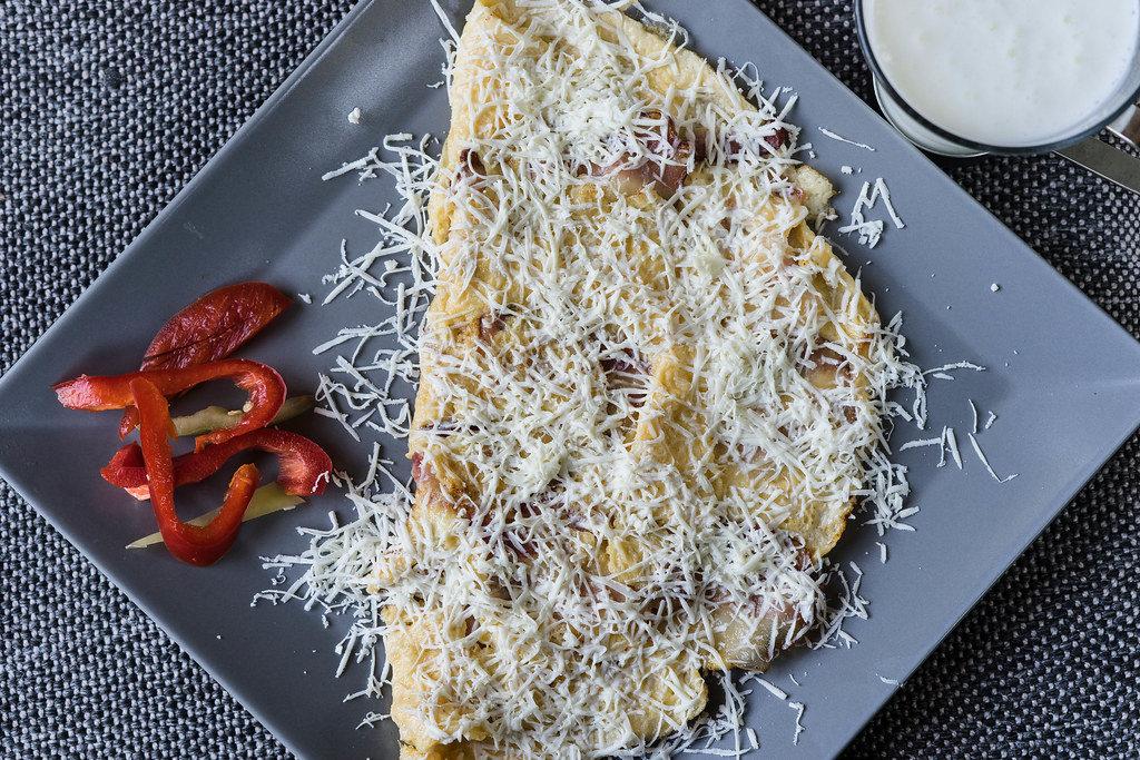 Omelett mit geriebenem Käse auf einem Teller. Draufsicht