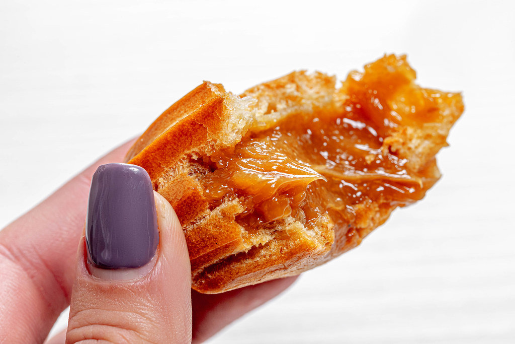 Close up of eclair with condensed milk in a womans hand