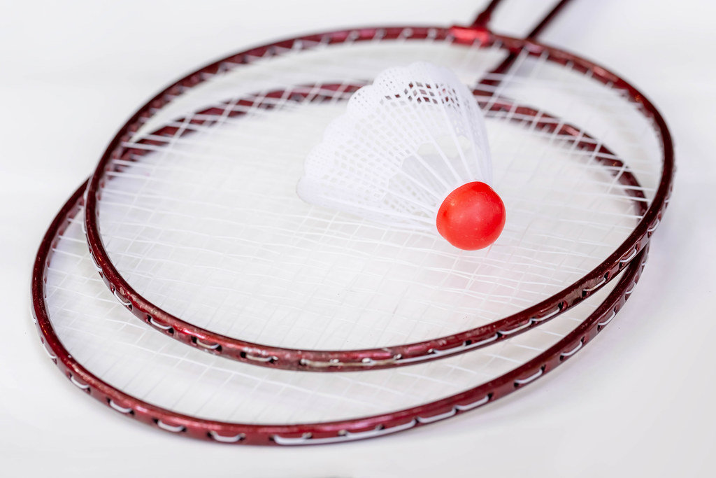 Red metal badminton rackets and a white shuttlecock