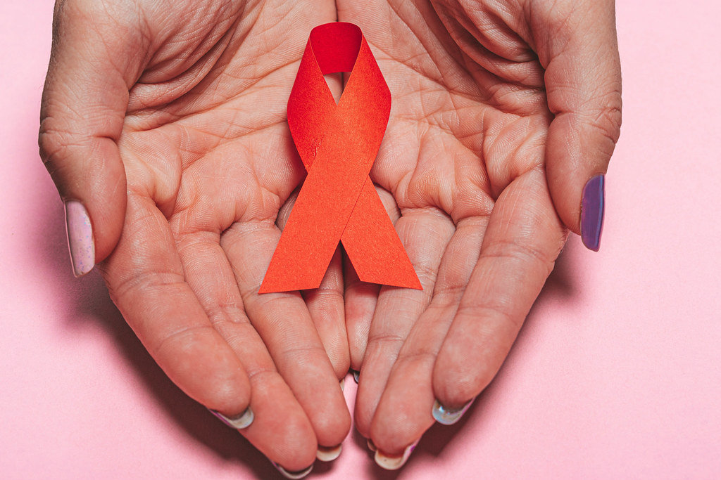 Healthcare, people, symbolic and medicine concept - close up of woman hands holding red AIDS awareness ribbon