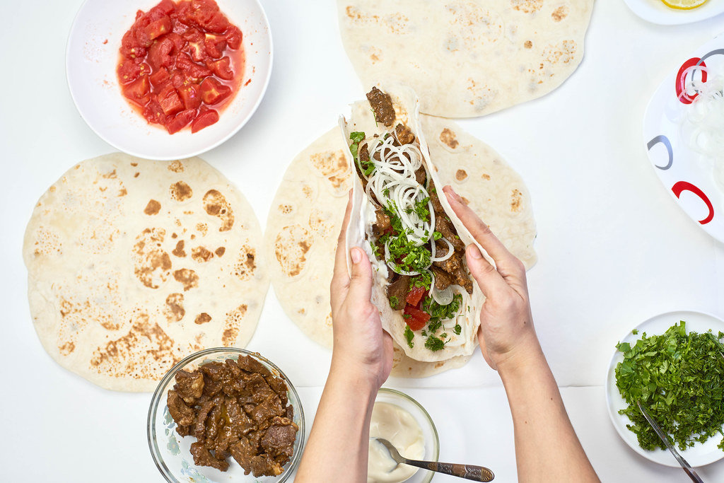 Woman preparing meat and vegetables based shawarma