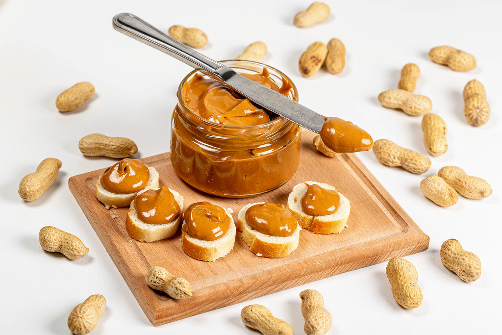 An open jar of peanut butter with sandwiches and peanuts