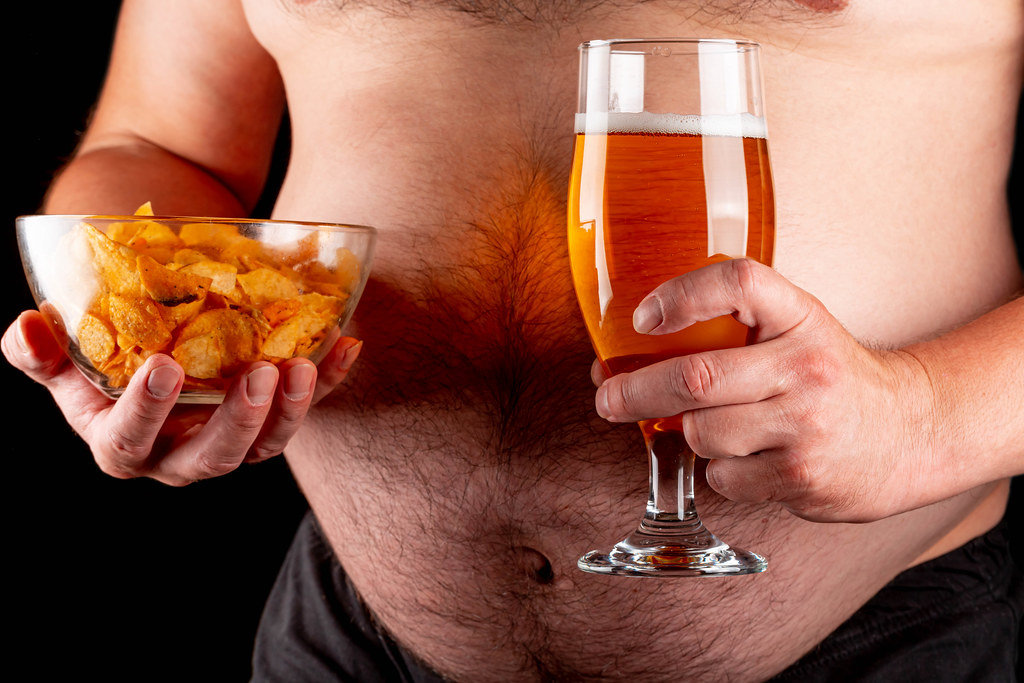 A man with a beer belly holds a glass of beer and chips