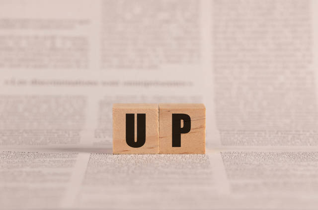 Up written with cubes on a newspaper